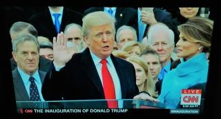 ▲親の代からの聖書の上に手を置き宣誓式に臨むトランプ新大統領(2017年1月20日、CNN放送の中継から)